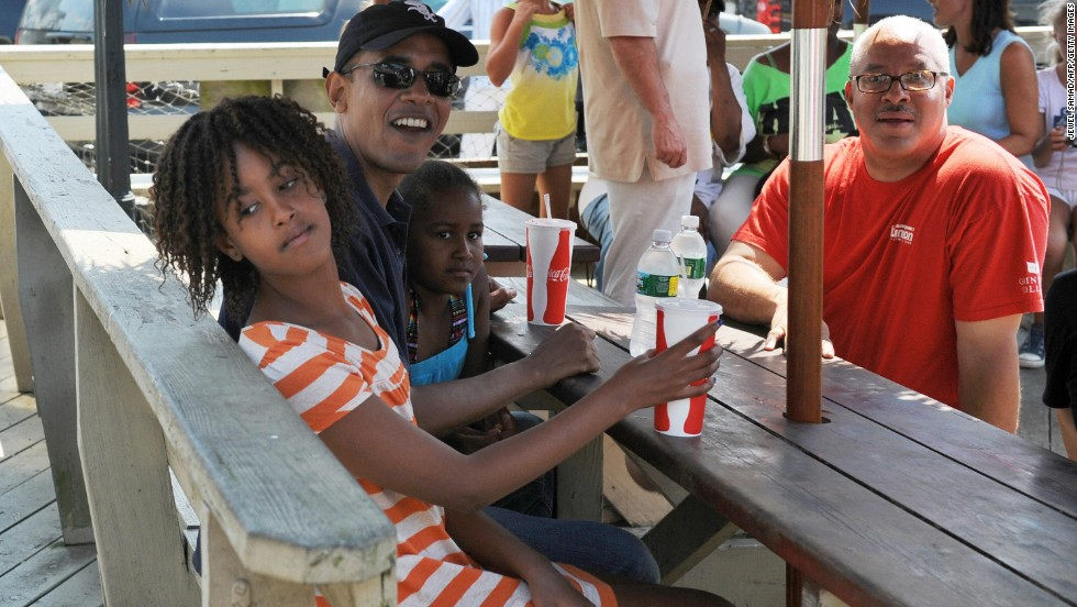 Obama waits for lunch with daughters Malia, left, and Sasha at a Martha's Vineyard restaurant in August 2009.