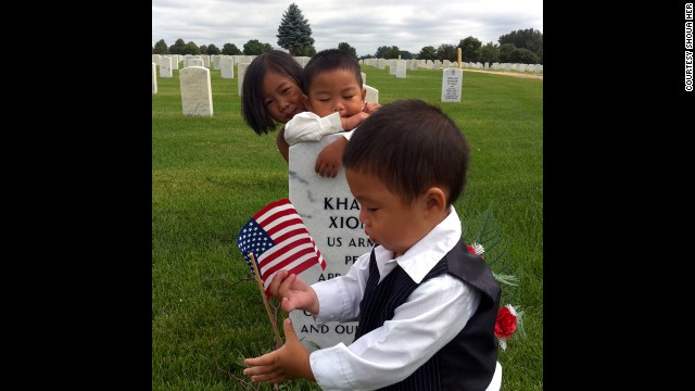 Kham Xiong's children visit their father's grave at Fort Snelling National Cemetery in Minnesota. Xiong was one of the 13 people killed in the Fort Hood shootings in 2009.