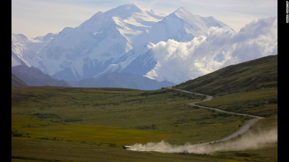 A tour bus kicks up dust during a sunny day at Denali National Park in Alaska on August 8.