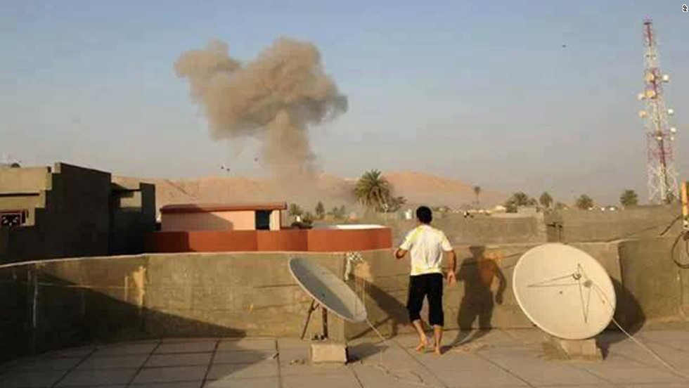 Smoke rising from a bomb attack in Tuz Khormato can be seen from a rooftop on August 10.