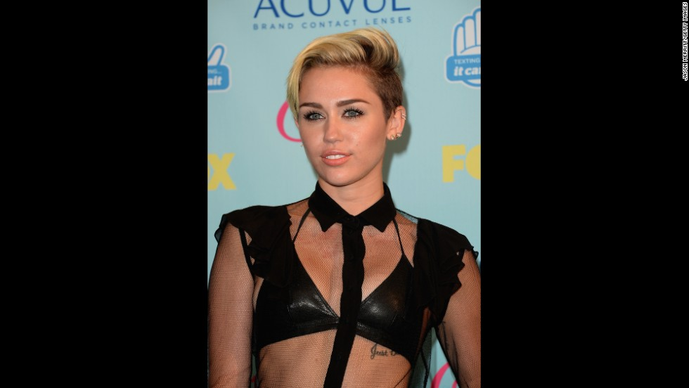 Miley Cyrus, wearing a revealing black number, attends the event.