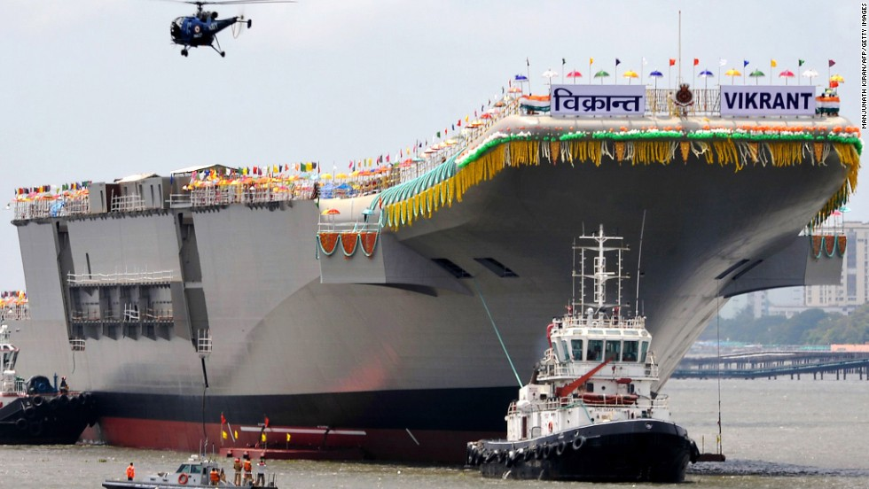 Tugboats guide aircraft carrier INS Vikrant as it leaves a shipyard after a launch ceremony in Kochi, India, on Monday, August 12. The 37,500-ton indigenous aircraft carrier will undergo extensive tests in the next few years before being commissioned into the Indian navy. The Vikrant is part of India's bid to join a select group of nations capable of building such warships -- the United States, United Kingdom, Russia and France.<br />