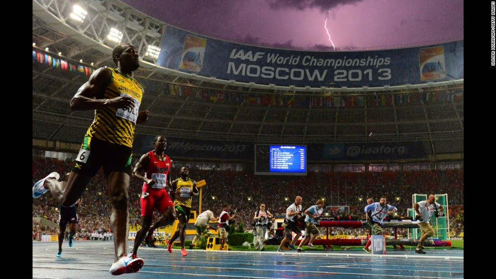 Jamaica's Usain Bolt wins the 100-meter final at the 2013 IAAF World Championships on August 11 as lightning flashes across the Moscow skies.