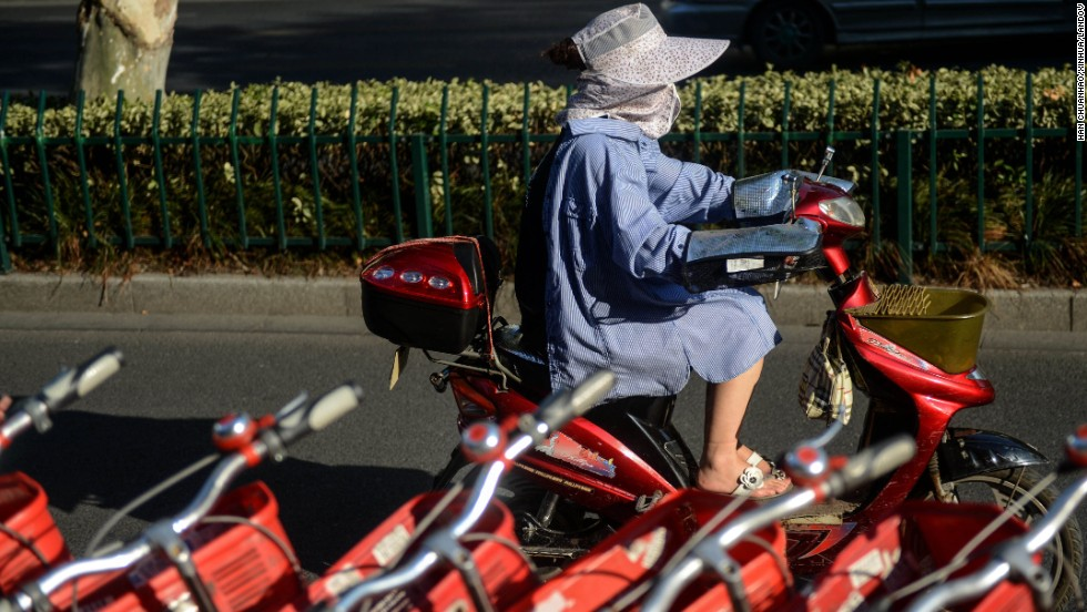 "A woman wears sun-protective clothing as she rides in Hangzhou, China, on Monday, August 12. <a href=""http://www.cnn.com/2013/08/13/world/asia/asia-heat/index.html"">Temperatures have spiked in Northeast Asia</a> this summer, causing heat-related deaths as well harming crops and livestock."