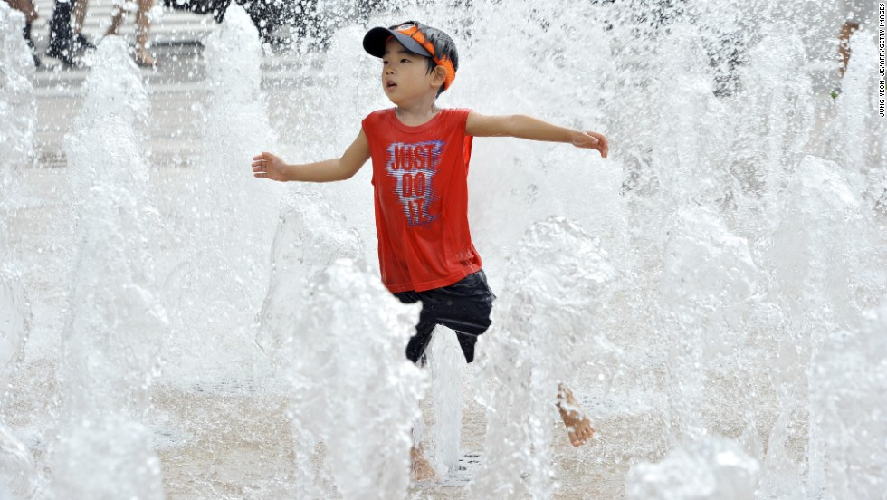 A South Korean boy plays in a fountain in Seoul on August 12.