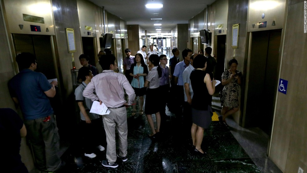 People wait for working elevators at a government building in Seoul, South Korea, on August 12. The hot weather has put a strain on South Korea's power grid, and the government ordered workers in government offices to turn off air-conditioning and avoid using some elevators.