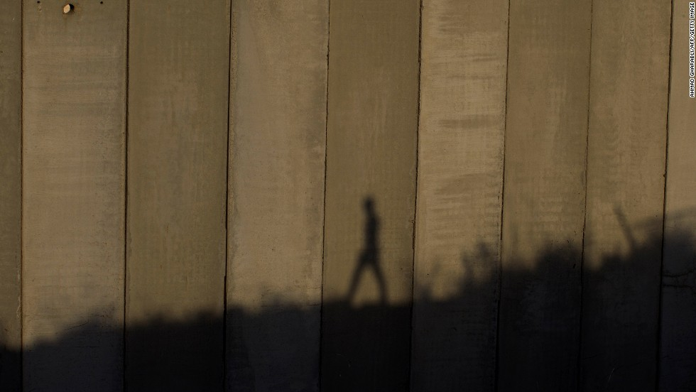 "AUGUST 13 - JERUSALEM: A man walks past the separation wall near Jerusalem's Shuafat camp. The Israeli government approved the building of <a href=""http://cnn.com/2013/08/13/world/meast/mideast-palestinians-israelis/index.html"">900 new settlement units</a> in East Jerusalem on Tuesday -- the day before <a href=""http://cnn.com/2013/07/19/world/meast/mideast-kerry-visit/index.html"">peace talks with Palestinians</a> were set to resume. The move has drawn fire from critics who say construction on disputed territory could derail the talks."