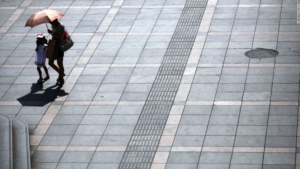 "A woman and a girl walk under an umbrella during <a href=""http://www.cnn.com/2013/08/13/world/asia/asia-heat‎/index.html"">a scorching summer heat wave</a> in Shanghai, China, on August 13."
