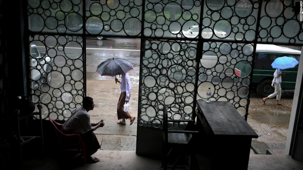 People make their way to work in the rainy weather in Yangon, Myanmar, on Monday, August 12.