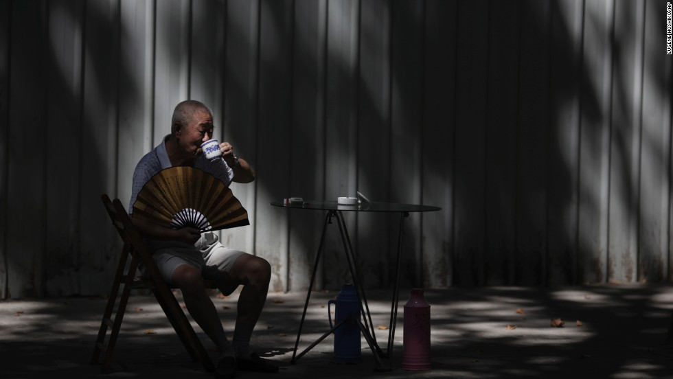 "A man sips tea while sitting in the shade to cool off at a park in Shanghai, China, on August 12. <a href=""http://www.cnn.com/2013/08/08/world/gallery/week-in-weather/index.html"">View last week's best weather photos.</a>"
