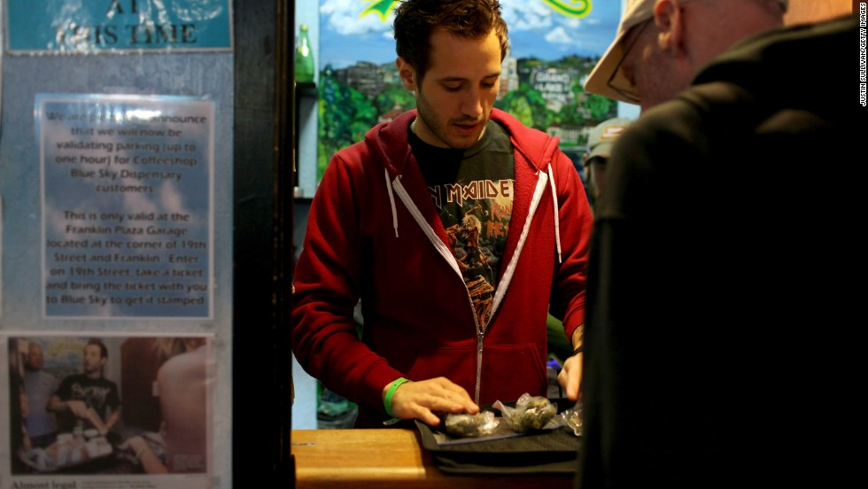Coffeeshop Blue Sky worker Jon Sarro, left, shows a customer different strains of medical marijuana on July 22, 2009, in Oakland, California. Voters in the city approved a measure during a vote-by-mail special election for a new tax on sales of medicinal marijuana at cannabis dispensaries.