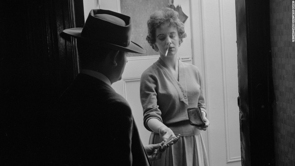 A woman buys ready-rolled marijuana cigarettes from a dealer at her door circa 1955.