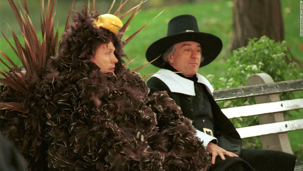 "Billy Crystal, left, dressed as a turkey, sits on a bench with De Niro, dressed as a pilgrim, during the filming of a Thanksgiving-themed ""I Love New York"" commercial in 2001."