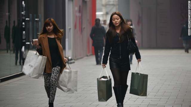 Two women walk with shopping bags in Beijing, China, on April 23.