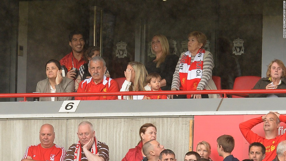 A smiling Luis Suarez (back left) attends Liverpool's opening fixture of the Premier League season. The Uruguayan striker is serving the fifth game of a 10-match ban for biting Branislav Ivanovic in a match against Chelsea last April. Suarez's future at Liverpool is in doubt following an acrimonious summer in which the striker has agitated for a move away from Merseyside. Liverpool insist the player is not for sale.