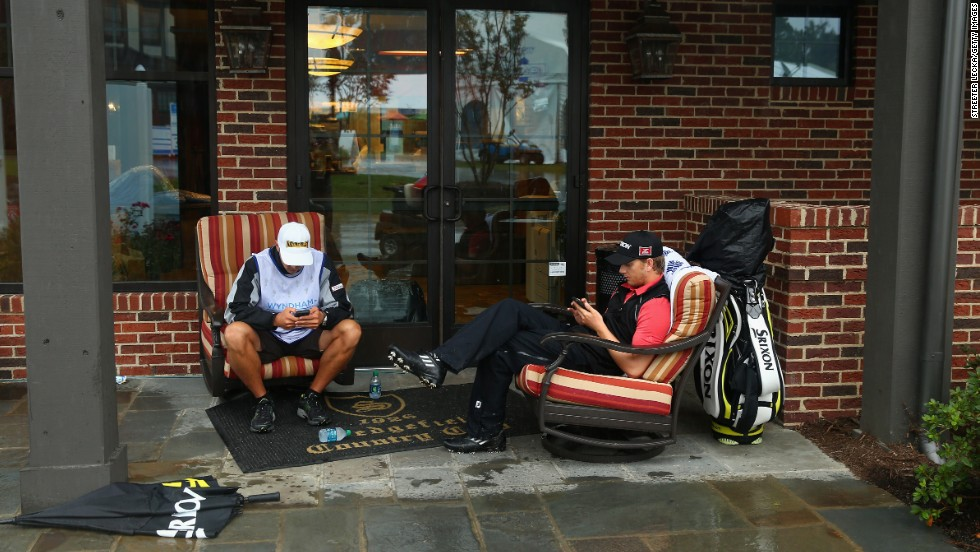 Chris Stroud, right, and his caddie check their phones during a weather delay on August 17 in the third round of the Wyndham Championship in Greensboro, North Carolina.