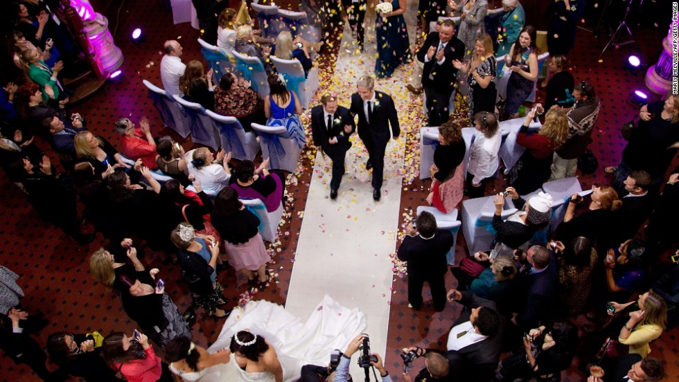 Richard Andrew, left, and Richard Rawstorn walk down the aisle after getting married at the Rotorua Museum on August 19. Including New Zealand, 14 countries now allow same-sex marriage.
