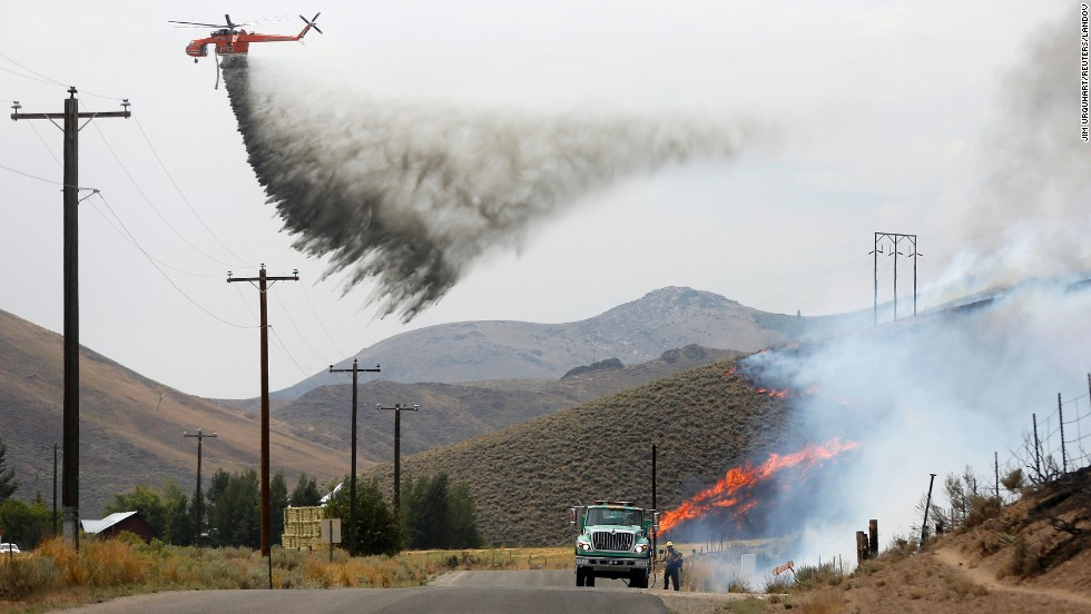 A tanker helicopter drops water as a firefighter works to douse a hot spot at Beaver Creek on August 17.