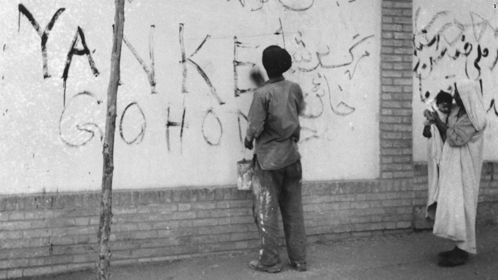 "A resident washes ""Yankee Go Home"" graffiti off a wall in Tehran on August 21, 1953. Zahedi ordered a clean-up after the coup."