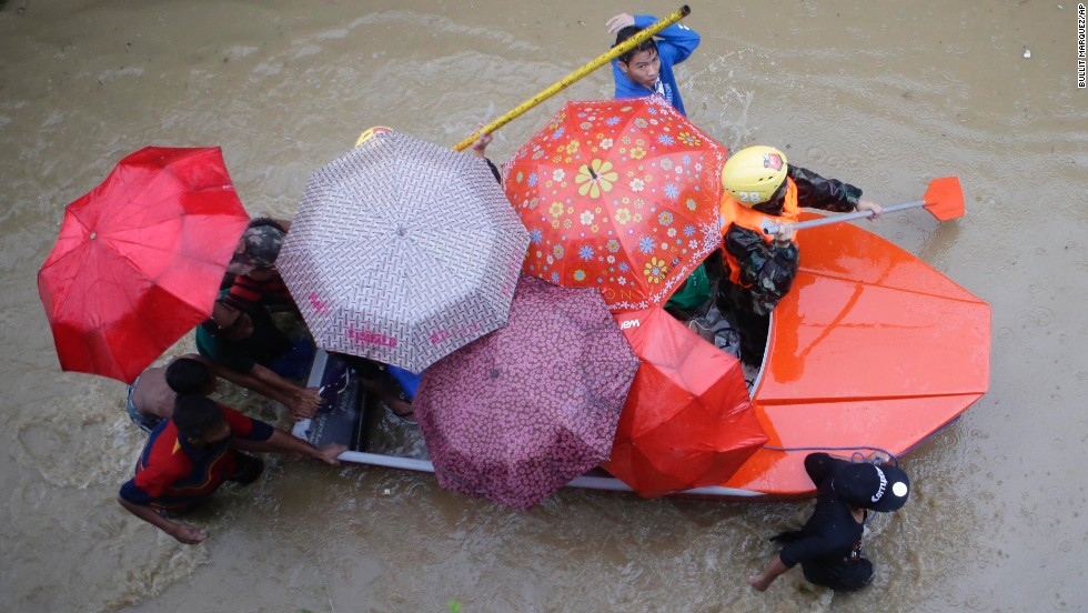 Members of the Philippine army paddle a boat with residents as they enforce an evacuation in Marikina City on August 20.