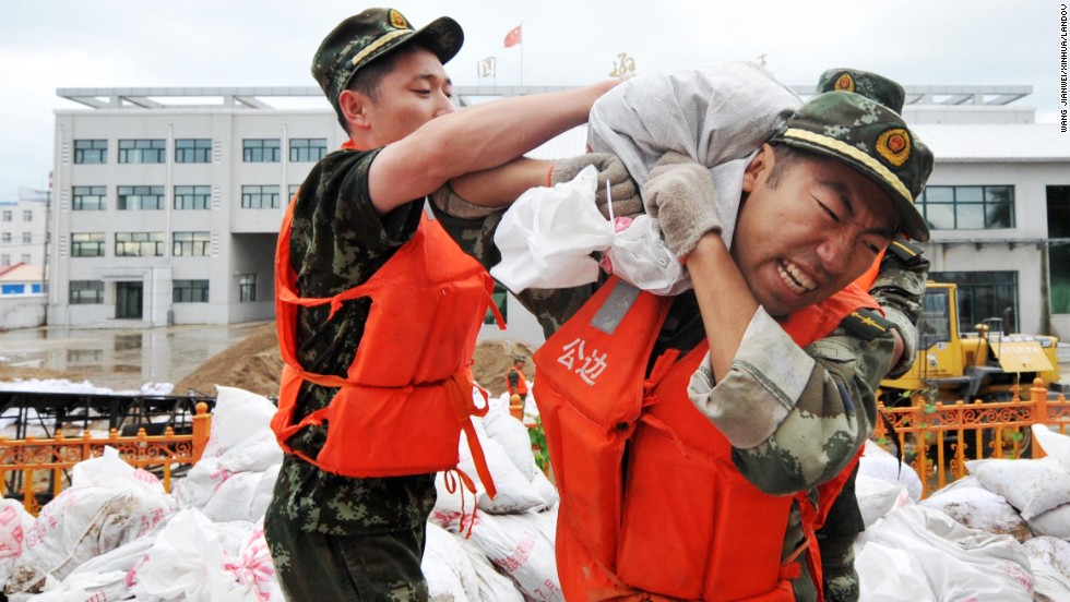 Soldiers carry sand bags for a barricade at the border crossing with Russia in Xunke County, China, on Saturday, August 17.