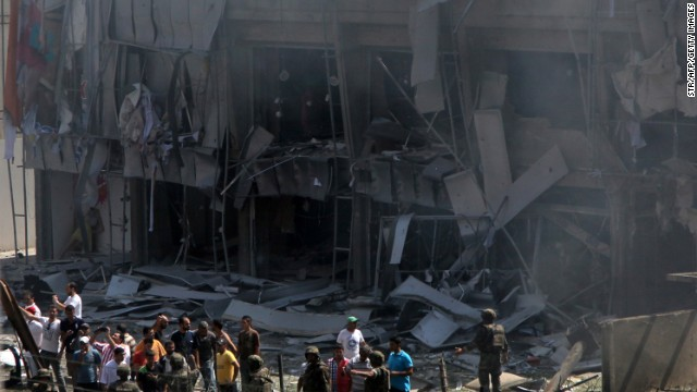 Lebanese citizens stand in front of the site of a powerful explosion in the northern Lebanese city of Tripoli on August 23, 2013.