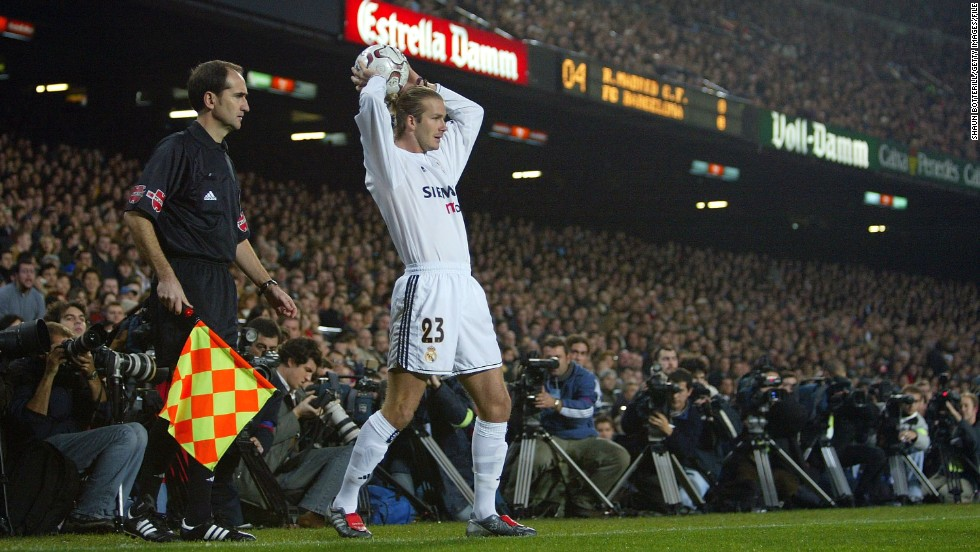 Football star and fashion icon David Beckham swapped Manchester United for Real in 2003. After four years in the Spanish capital, Beckham headed to the United States, joining the Los Angeles Galaxy.<br /><br /><br /><br />BARCELONA, SPAIN - DECEMBER 6: David Beckham of Real Madrid gets set for a throw in as he is closely watched by the media during the Spanish Primera Liga match between Barcelona and Real Madrid at the Nou Camp Stadium on December 6, 2003 in Barcelona, Spain.