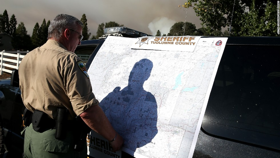 A Tuolumne County sheriff's deputy looks at an incident map of the Rim Fire on August 22, in Groveland, California.