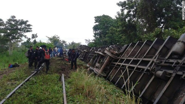 People inspect the derailed cargo train in Huimanguillo, Mexico, on Sunday, August 25.