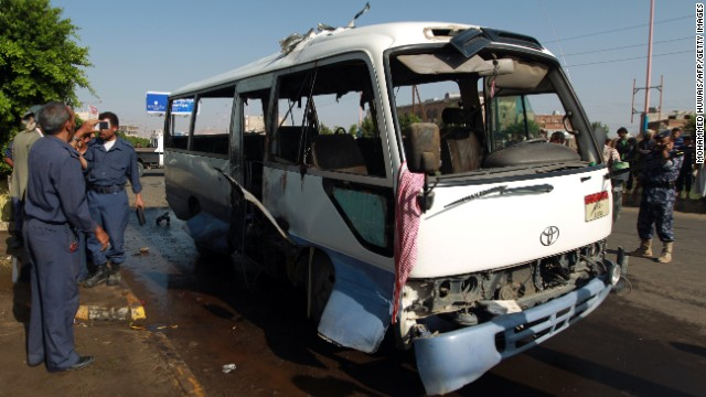Yemeni security forces inspect a damaged military bus following a bomb blast in Sanaa on Sunday.