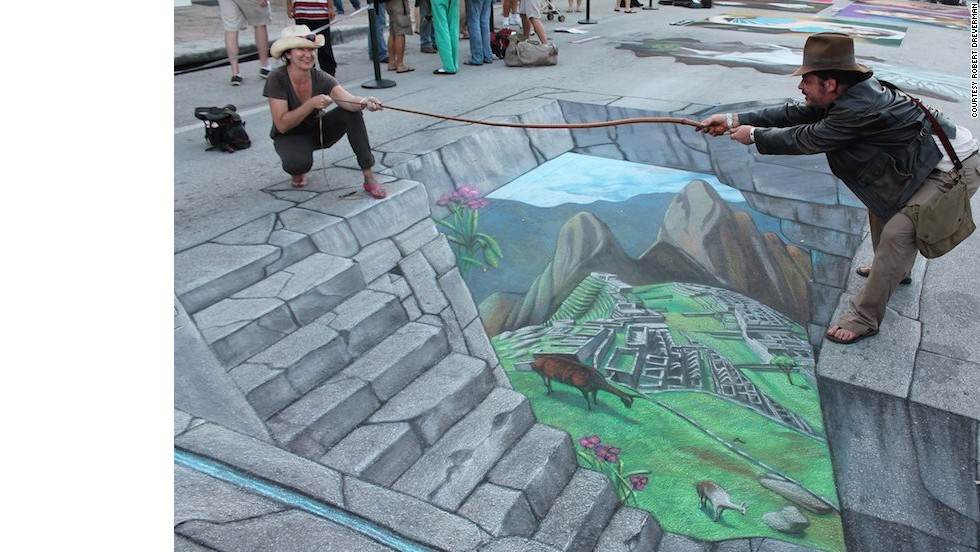 Tracy Lee Stum pulls fellow artist Kelly McClain into her 3D image of Machu Picchu in Lake Worth, Florida.