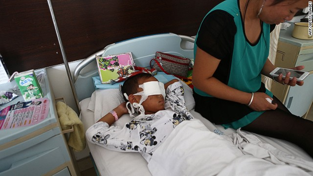 A boy lies  with his eyes bandaged as his mother sits next to him at a hospital in Taiyuan, Shanxi province, China.