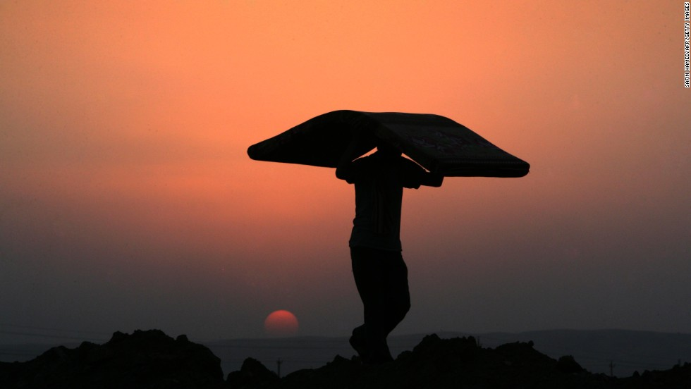 A Syrian Kurdish man carries a mattress at sunset at the Quru Gusik refugee camp in Iraq in August 2013.