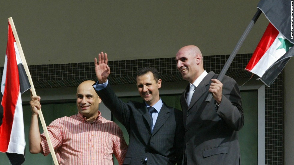 Two unidentified supporters of al-Assad join him on the balcony as he celebrates the referendum results in Damascus on May 29, 2007. Al-Assad won a second seven-year mandate after netting 97% of the vote in a referendum boycotted by the opposition.