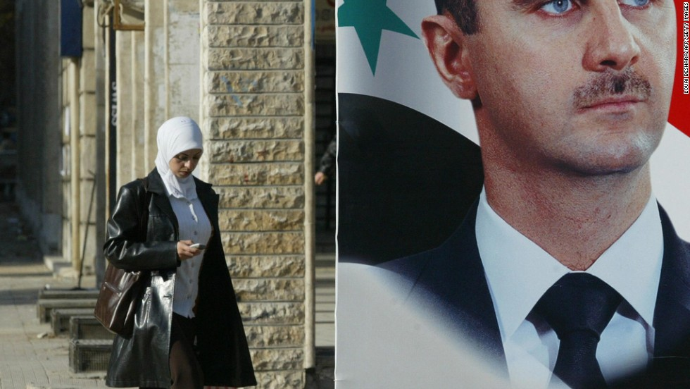 A Syrian woman walks past a large portrait of President al-Assad in downtown Damascus on December 13, 2005.