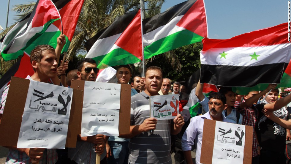 Palestinians, waving the Syrian and Palestinian national flags, demonstrate against possible Western military intervention in Syria in the West Bank city of Nablus on August 29.