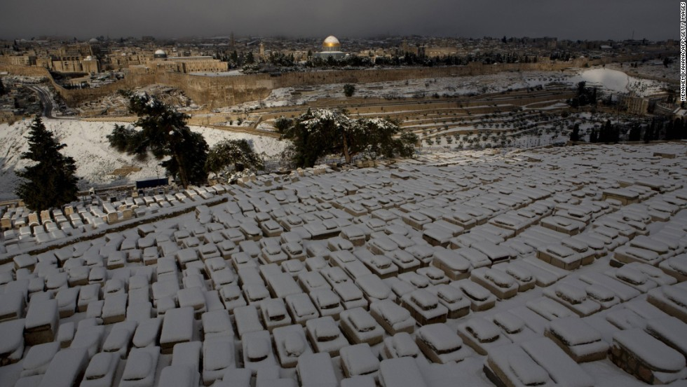 Tombs sit covered in snow at the Jewish cemetery at the Mount of Olives. There are spectacular views at the summit.