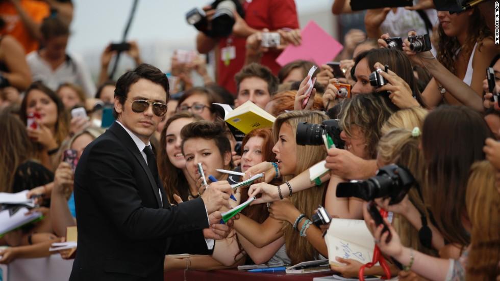 "James Franco signs autographs as he arrives for the film ""Palo Alto."""