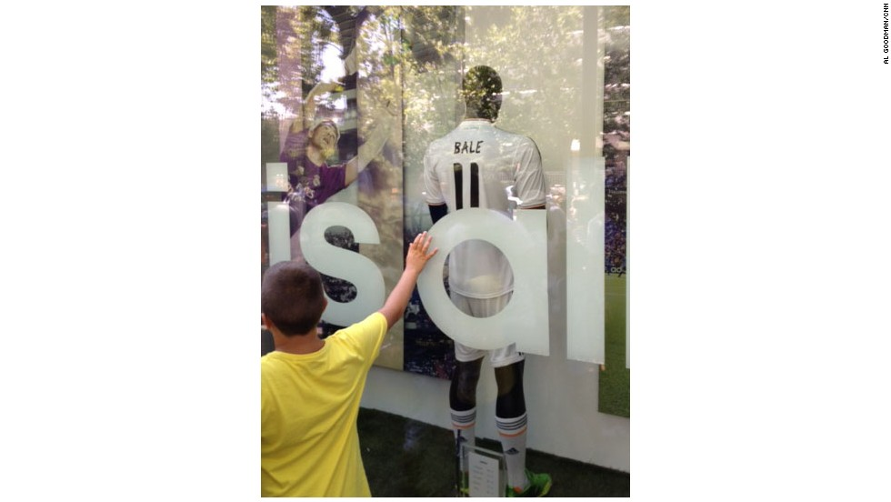A young fan paws the window of the Real Madrid shop showcasing Gareth Bale's new shirt.