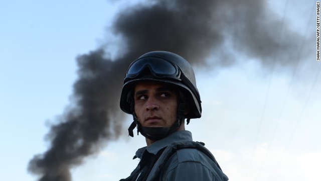 (File) Afghan policeman stand guard at the site of a suicide attack in Kabul on July 2, 2013.