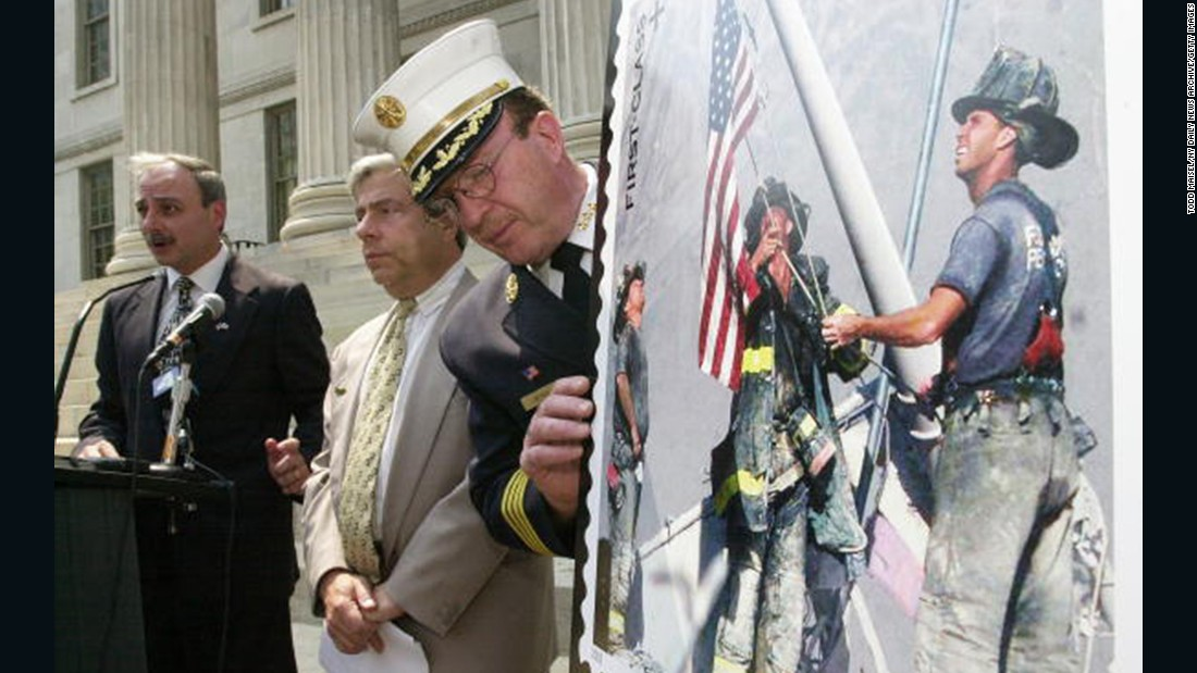 The stamp is displayed at a ceremony outside of the Brooklyn Borough Hall in New York on July 2, 2002. From left, Brooklyn Postmaster Joseph Lubrano, Borough President Marty Markowitz and Harold Meyers of the New York City Fire Department were in attendance.