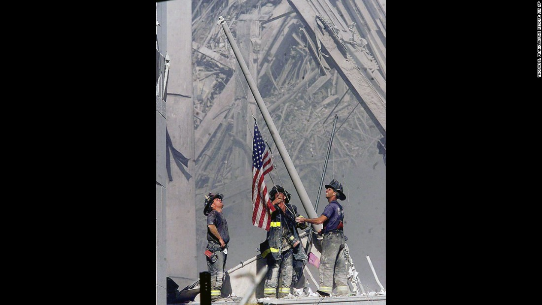"Firefighters George Johnson, Dan McWilliams and Billy Eisengrein raise a flag at ground zero in New York after the terror attacks on September 11, 2001. The scene was immortalized by photographer Thomas E. Franklin. The image has been widely reproduced in the decade since it was first published. <a href=""http://www.cnn.com/2013/09/01/world/gallery/iconic-images/index.html"">View 25 of history's most iconic photographs.</a>"