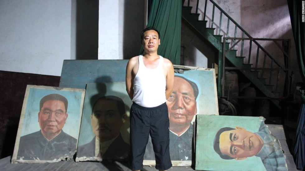 A superintendent of the former Workers' Theatre proudly looks after old images of (L-R) Hua Guofeng, Sun Yatsen, Mao Zedong and Zhou Enlai.