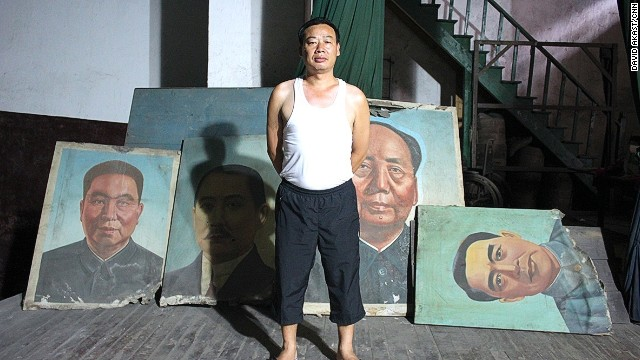 A superintendent of the former Workers' Theatre proudly looks after old images of Hua Guofeng, Sun Yatsen, Mao Zedong and Zhou Enlai.