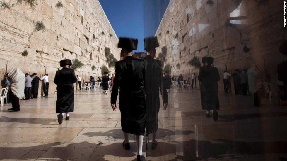 Orthodox Jewish men walk along the Western Wall on September 4.