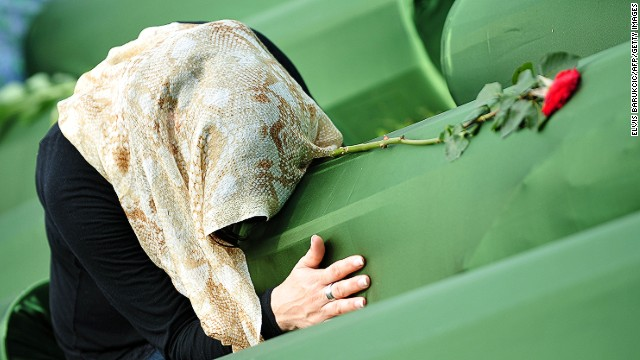 A Bosnian Muslim woman, survivor of Srebrenica 1995 massacre, mourns near the body caskets of her relatives at a memorial cemetery in the village of Potocari near the eastern Bosnian town of Srebrenica on July 11, 2013.
