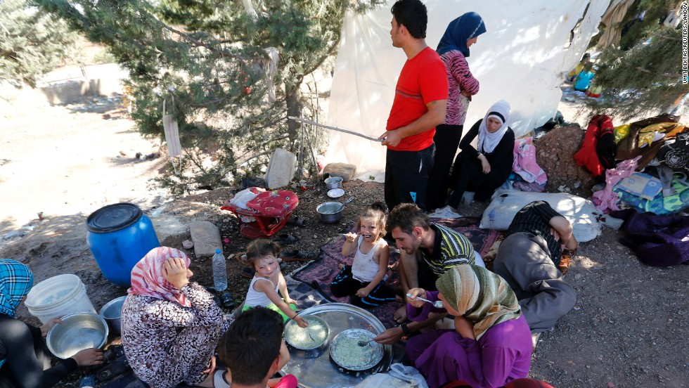 Syrian refugees who failed to find shelters at a refugee camp eat and rest by the side of a road a few feet away in September 2013.
