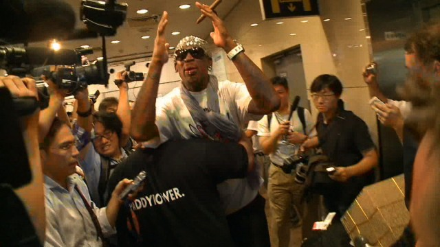 Security rushes away Dennis Rodman in Beijing after he is mobbed by reporters asking about his second trip to North Korea in a year.