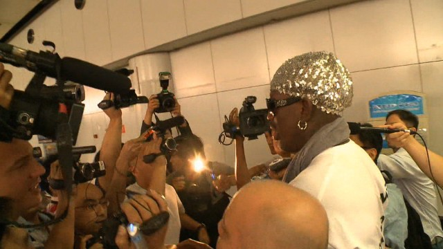 Flashing cameras and reporters' questions greet Dennis Rodman in Beijing September 7, 2013 after his second trip to North Korea in a year.
