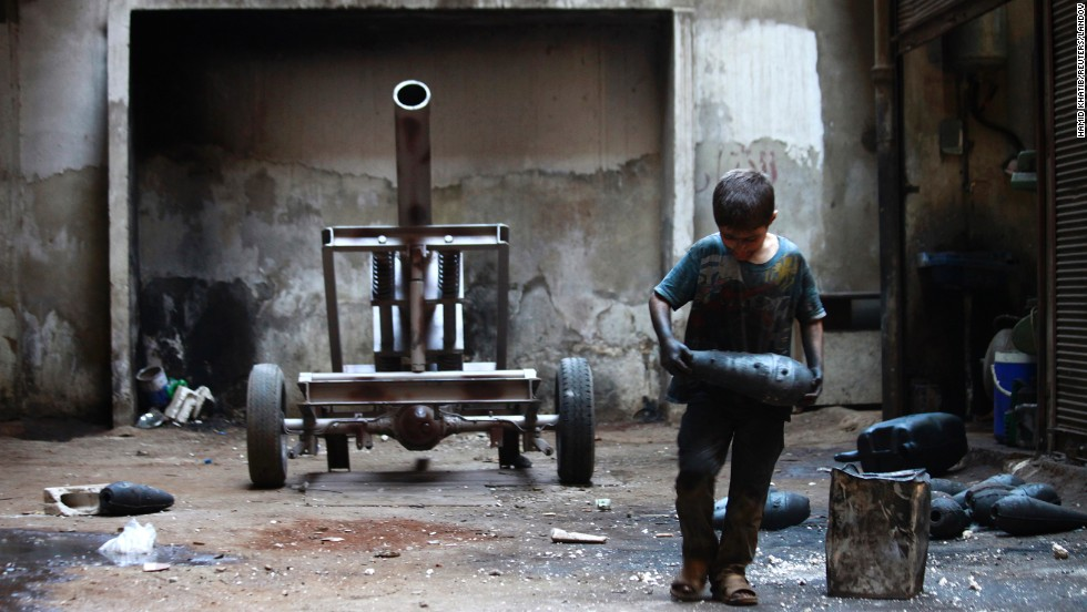 "<a href=""http://www.cnn.com/2013/09/09/world/gallery/issa-syria/index.html"" target=""_blank"">A boy named Issa</a>, 10, carries a mortar shell in a weapons factory of the Free Syrian Army in Aleppo on Saturday, September 7. The boy works with his father in the factory."